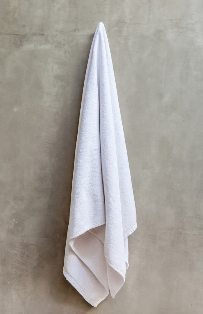 White towel is hanging on the exposed concrete wall in the bathr