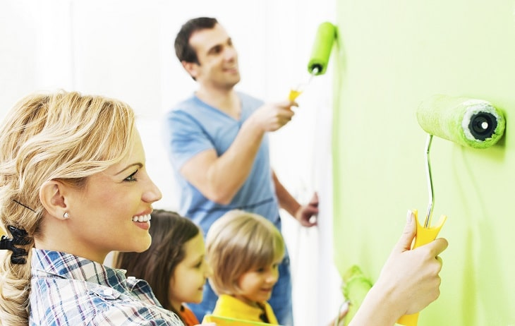Happy family painting walls.