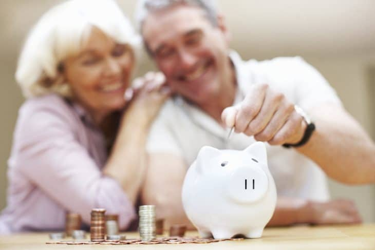 Portrait of happy mature couple saving money at home